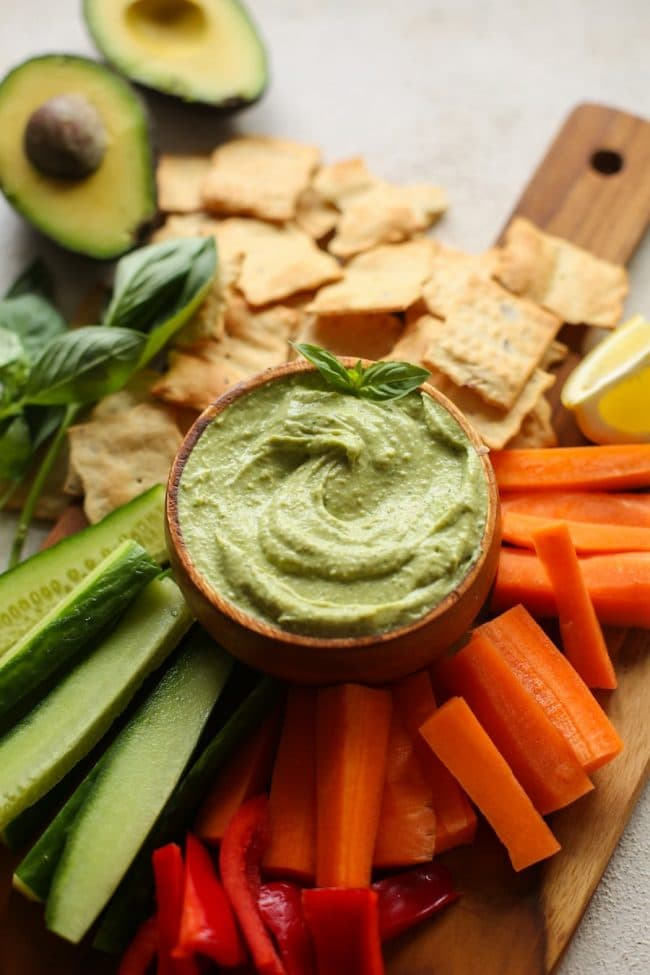 Basil Avocado Dip on a serving platter with fresh veggies