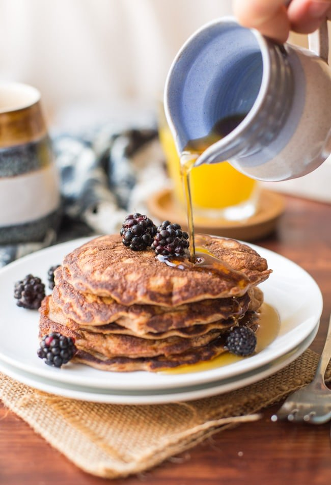 Coconut Flour Pancakes with maple syrup pouring over the top