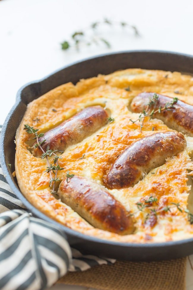 Gluten Free Toad in the Hole in a cast iron skillet with a stripped kitchen towel