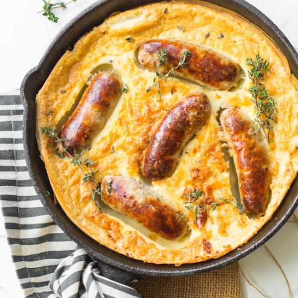 gluten free toad in the hole in a cast iron skillet topped with fresh thyme