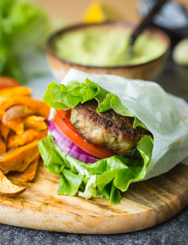 paleo turkey burger in a lettuce wrap with tomato and onion