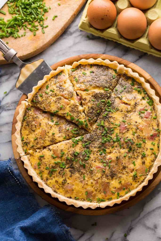 Dairy Free Quiche Lorraine (Low FODMAP) on a platter with slices cut out