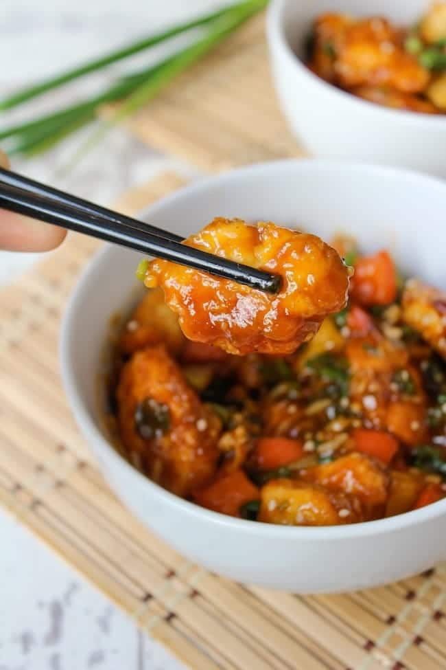 Paleo & Low FODMAP Sweet and Sour Chicken held up with chopsticks