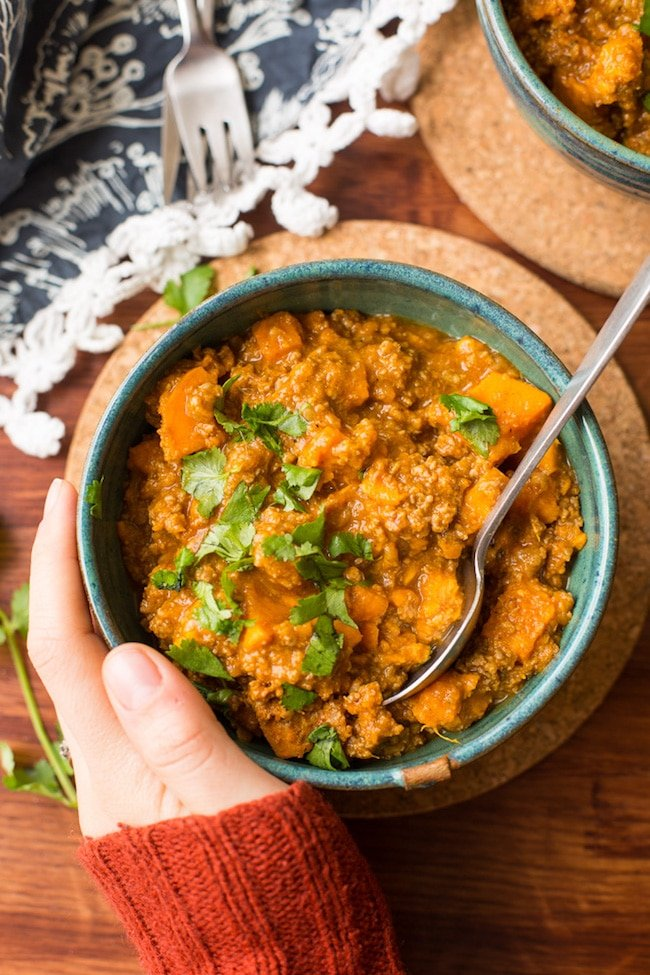 hand holding Paleo Chili Sweet Potato in a bowl