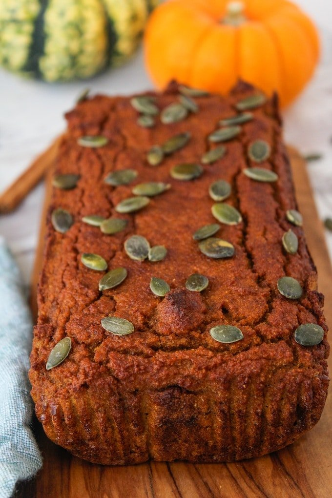 Paleo Pumpkin Bread topped with pepitas with a small baby pumpkin in the background