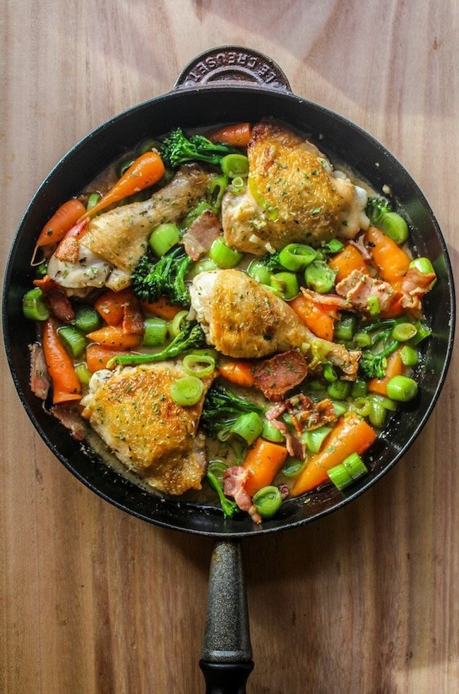 white wine braised chicken and veggies in a cast iron pan