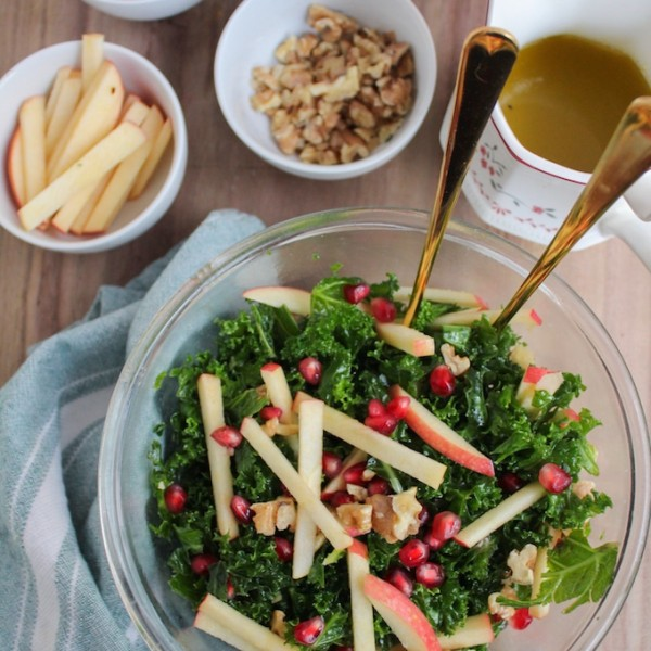 Winter Kale Pomegranate Salad: crisp apples, toasted walnuts, massaged kale and ruby red pomegranate seeds topped in a sweet and tangy honey mustard dressing.