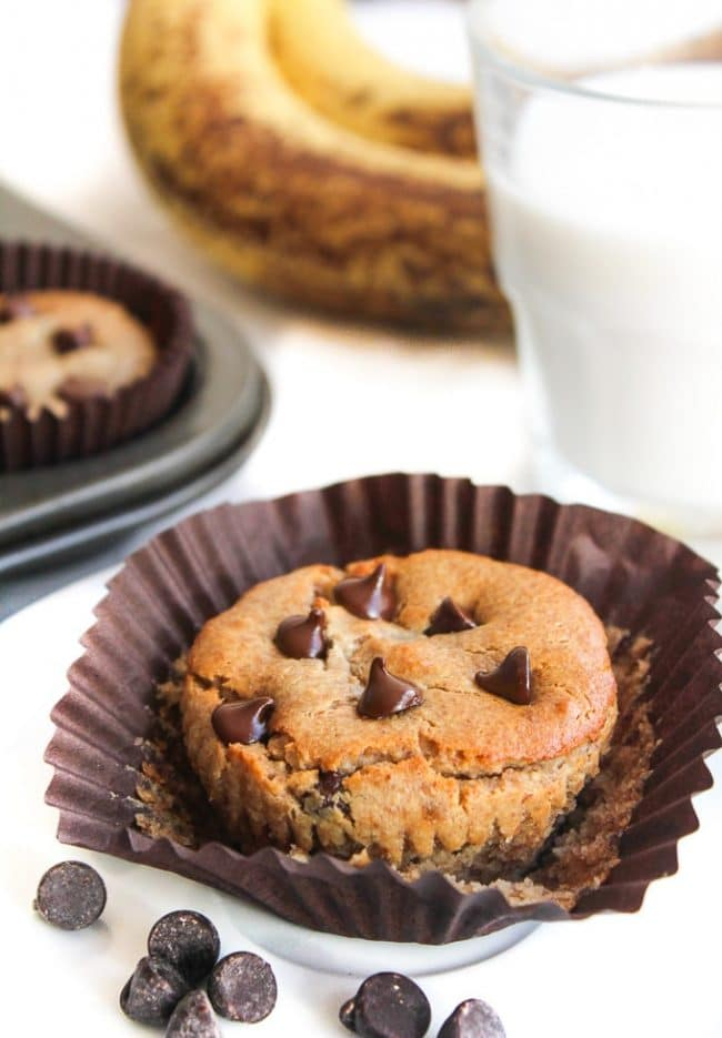 almond butter blender muffin topped with chocolate chips next to a glass of almond milk