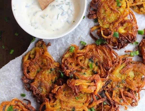 crispy onion bhajis on baking paper with a yoghurt dip