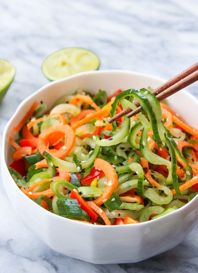 Asian Cucumber Sesame Salad in a bowl with chopsticks holding noodles up