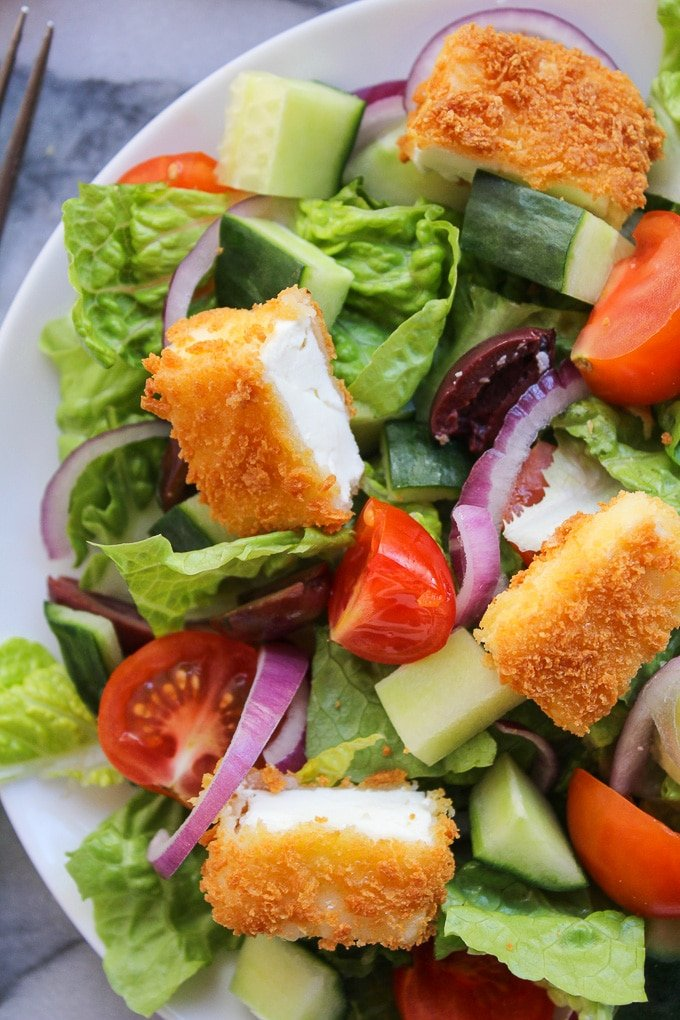 Crunchy Greek Salad topped with crispy fried feta coated in gluten free bread crumbs and dressed in a delicious red wine, lemon, and garlic herb vinaigrette