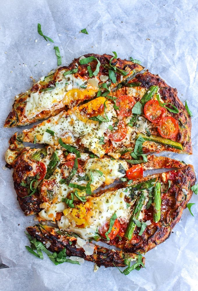 Zucchini Crusted Breakfast Pizza topped with sliced asparagus, cherry tomatoes, eggs, and a sprinkling of parmesan cheese.