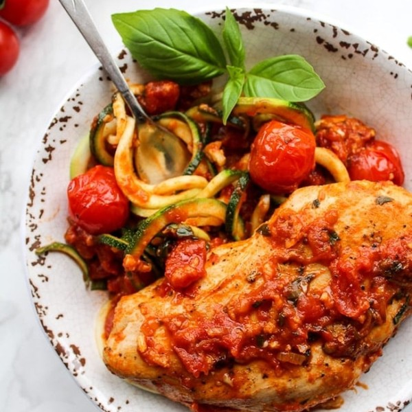 Tomato Basil Garlic Chicken over zucchini noodles in a bowl garnished with basil
