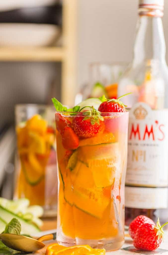 pimm's cup with fresh strawberries and cucumber in a glass