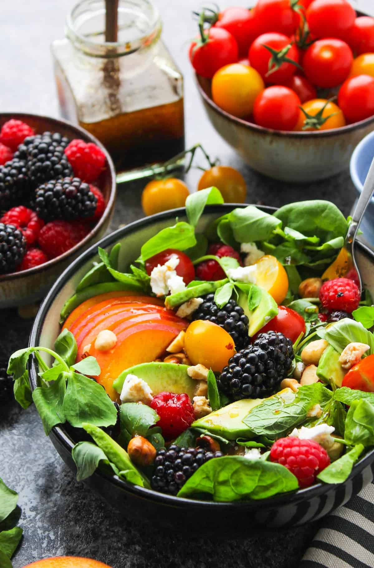 summer salad in a bowl with peach slices, blackberry and avocado