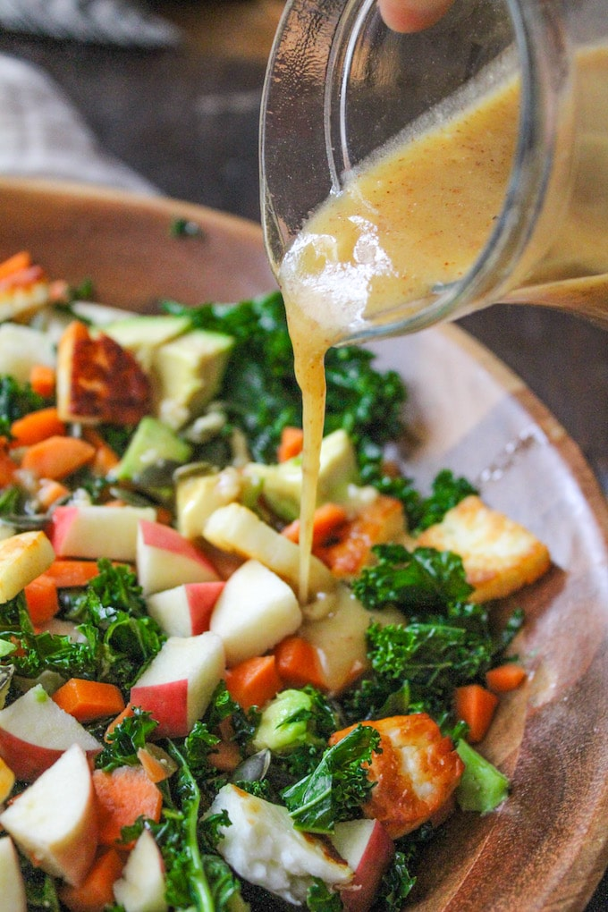 Crunchy Carrot Apple & Massaged Kale Salad topped with halloumi, avocado, seeds and a mustardy almond butter dressing | grain free + gluten free + vegetarian