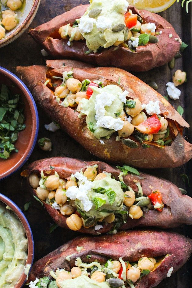 Mediterranean stuffed sweet potatoes with marinated chickpeas and topped with an avocado tahini sauce