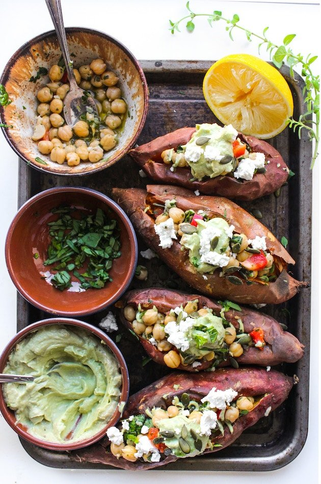 Mediterranean stuffed sweet potatoes on a tray with herbs, avocado tahini and chickpeas