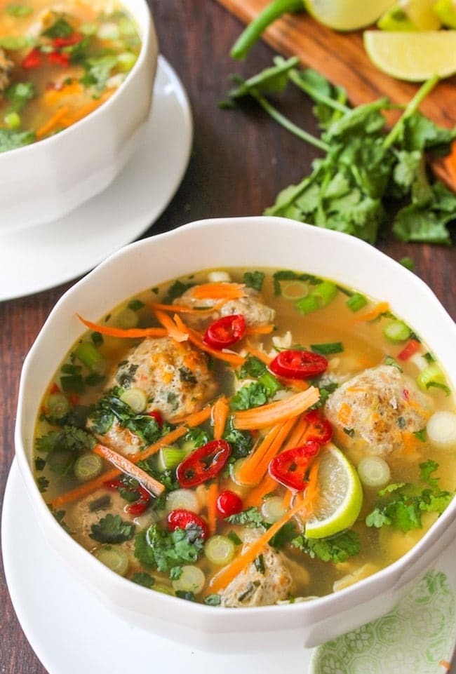 Thai-Meatball-Soup in a white bowl surrounded by cilantro