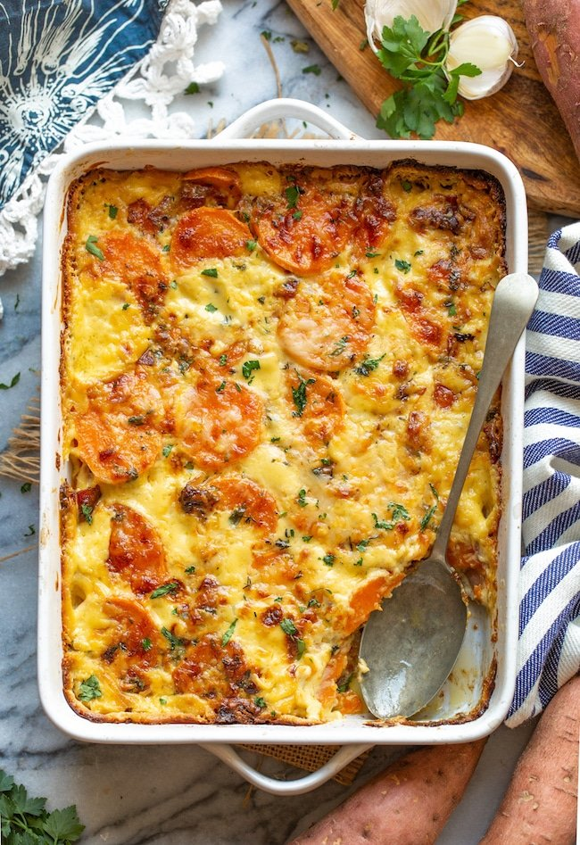 scalloped sweet potatoes in a baking dish with a serving spoon