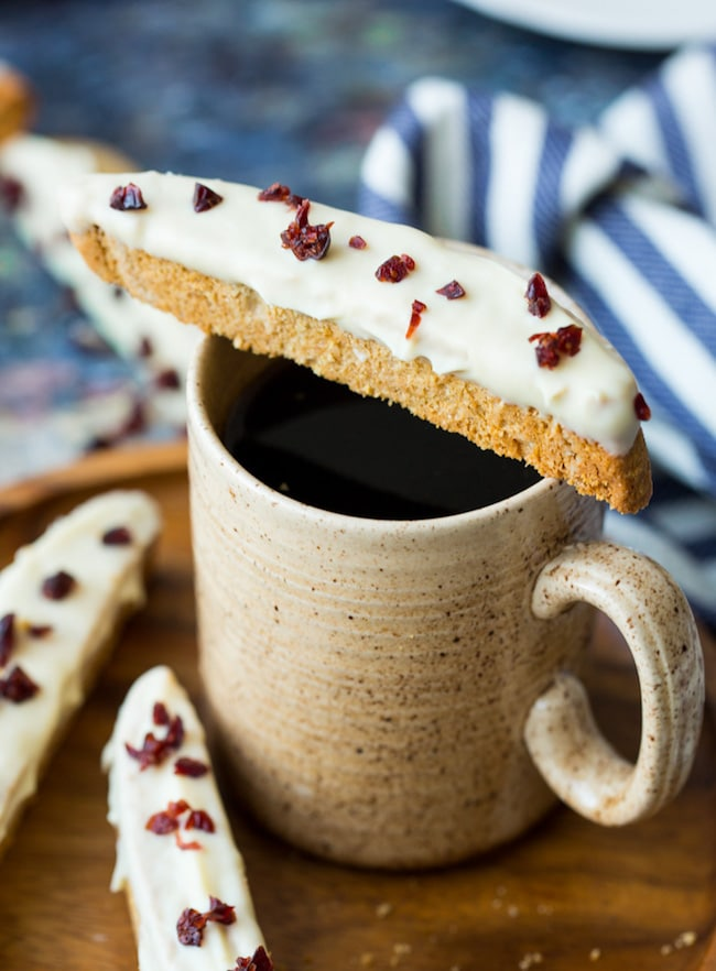 cranberry bliss gluten free biscotti sitting on top of cup of coffee