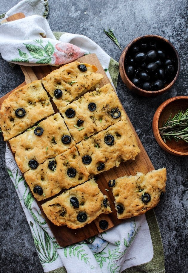 Gluten Free Focaccia Flatbread topped with sliced black olives and fresh rosemary. Made Vegan with aquafaba instead of eggs