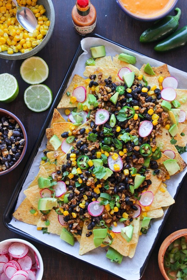 Easy, cheesy, plant based Vegan Nachos loaded with veggies, stretchy nacho cheese, and a black bean-walnut 'meat'. Gluten Free + Dairy Free
