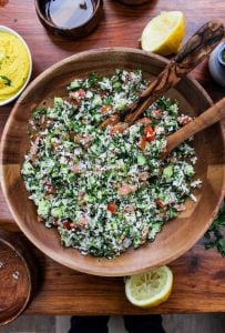 Paleo Cauliflower Tabbouleh in a wooden bowl with salad spoons