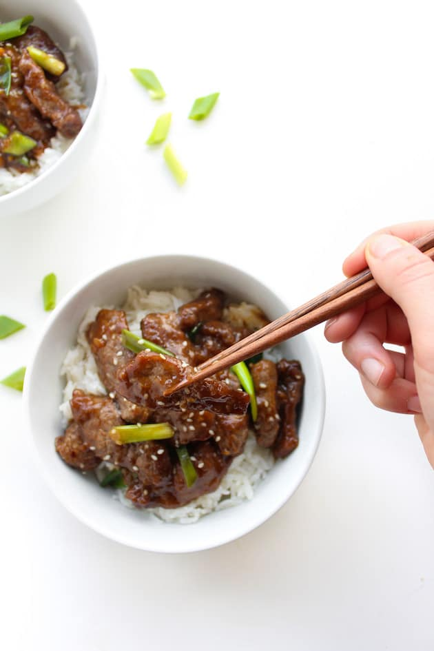 Paleo Mongolian Beef in a bowl topped with spring onions and chop sticks pick a piece up