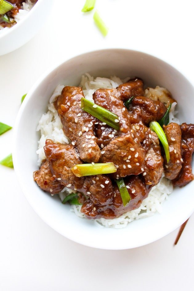 Paleo Mongolian Beef in a bowl topped with spring onions
