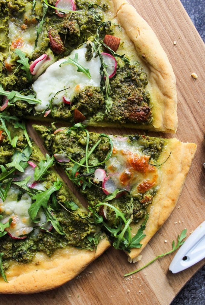 Super Green Kale Pesto Pizza topped with arugula, sliced radishes, chopped almonds and dollops of mozzarella. Gluten Free + Vegetarian