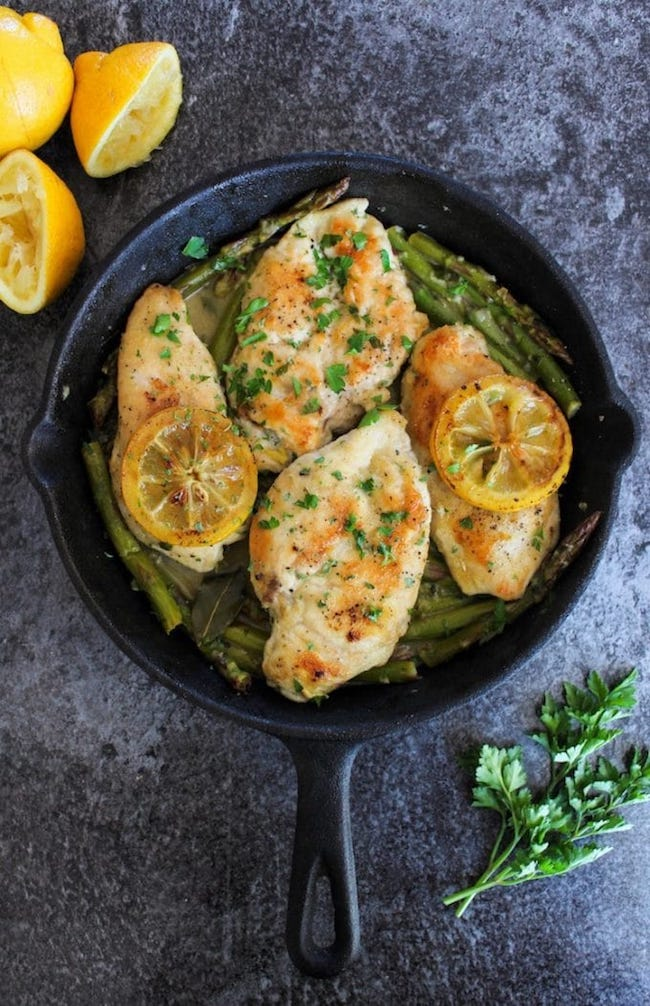 One Pan Lemon Chicken in a cast iron skillet topped with grilled lemons and parsley