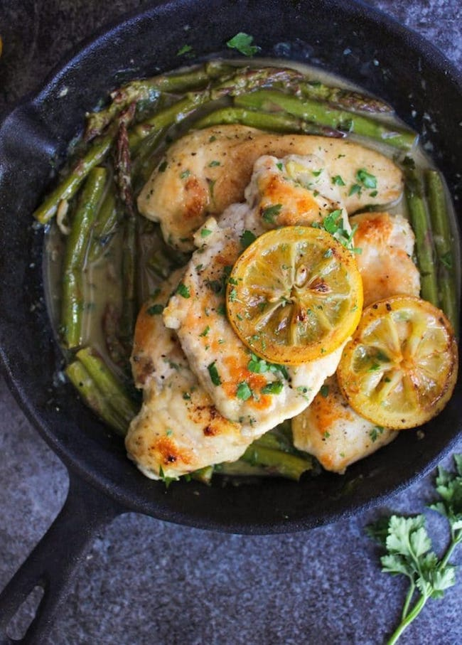 One Pan Lemon Chicken in a cast iron skillet topped with grilled lemons and parsley with asparagus