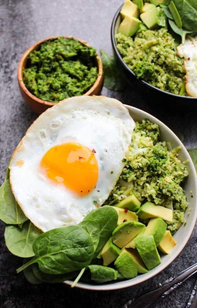 Pesto Cauliflower Rice Bowls topped with eggs and avocado