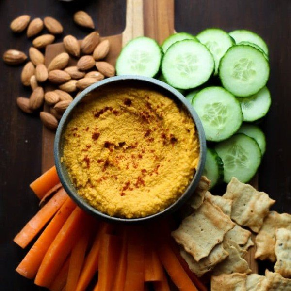 Roasted Carrot Hummus on a serving board with chips and sliced veggies
