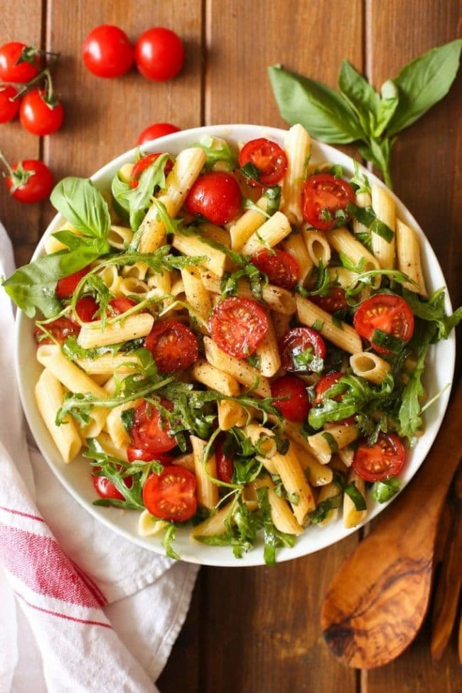 Tomato & Arugula Balsamic Pasta Salad topped with basil in a bowl