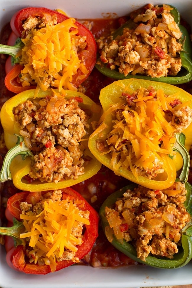 taco stuffed peppers in a baking dish before cooked