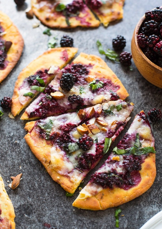 sliced blackberry flatbread pizzas on a granite background topped with basil and almonds