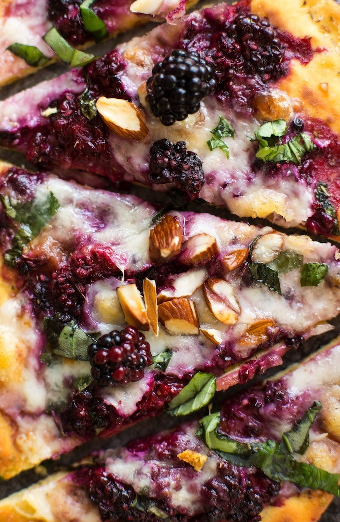 up close blackberry flatbread pizza sliced on a granite background topped with basil and almonds