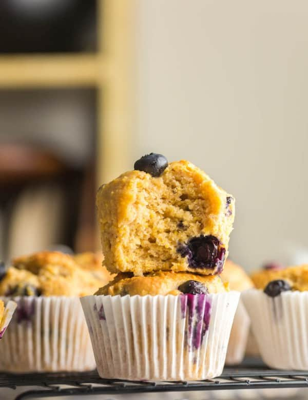 two Gluten Free Blueberry Cornbread Muffins stacked on a cooling rack