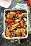 Easy One Pan Greek Chicken with Roasted Veggies in a baking dish on a kitchen napkin