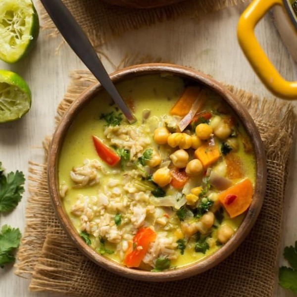 Chickpea Lime & Coconut Soup in a wooden bowl with limes on the side