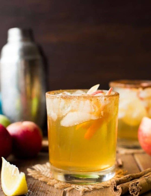 Apple Margarita in a glass with apple slices surrounded by cinnamon sticks