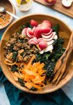 Crunchy kale apple salad in a salad bowl with salad tongs