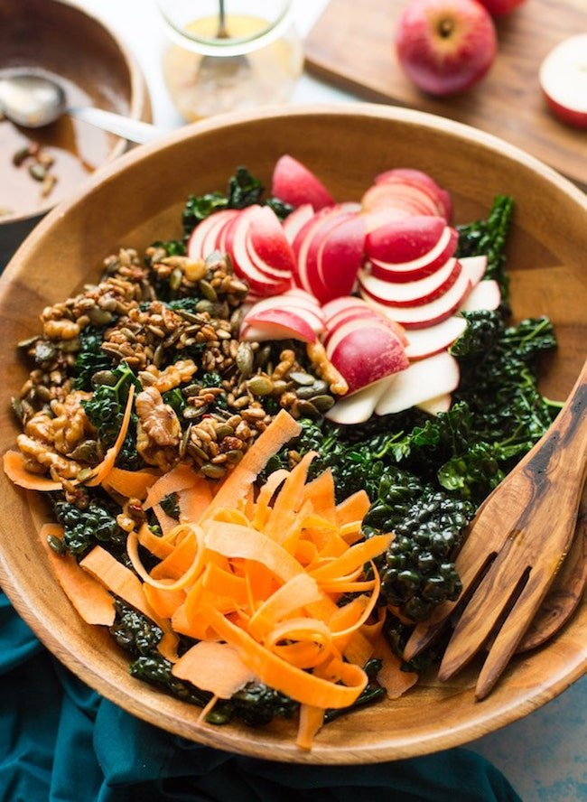Crunchy kale apple salad in salad bowl: carrot, apple, nut + seed mixture