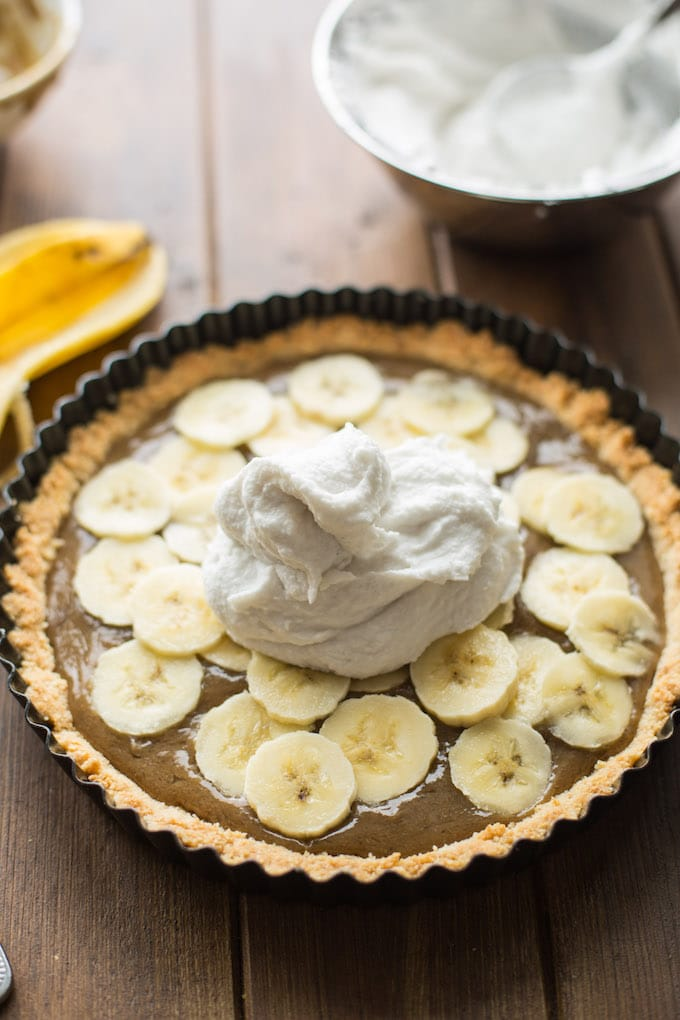 Rich and decedent Vegan Banoffee Pie - a simple, almond flour crust topped with silky caramel, banana, coconut whipped cream and a drizzle of chocolate | Gluten Free + Paleo| Spreading coconut cream over the top of the pie