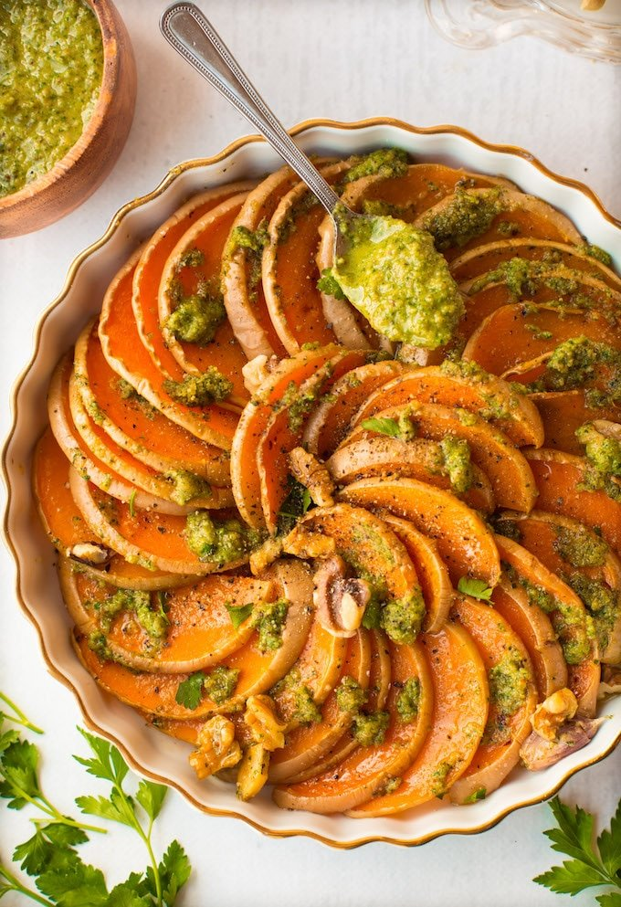 Tender roasted butternut squash slices with a simple parsley pesto and topped with pieces of walnut for added crunch! Gluten Free + Vegan + Whole30 | with spoon of pesto