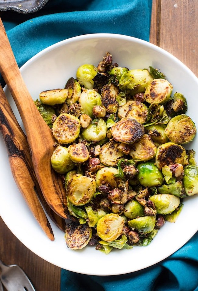 sauteed brussels sprouts with mustard and hazelnuts in a white serving bowl