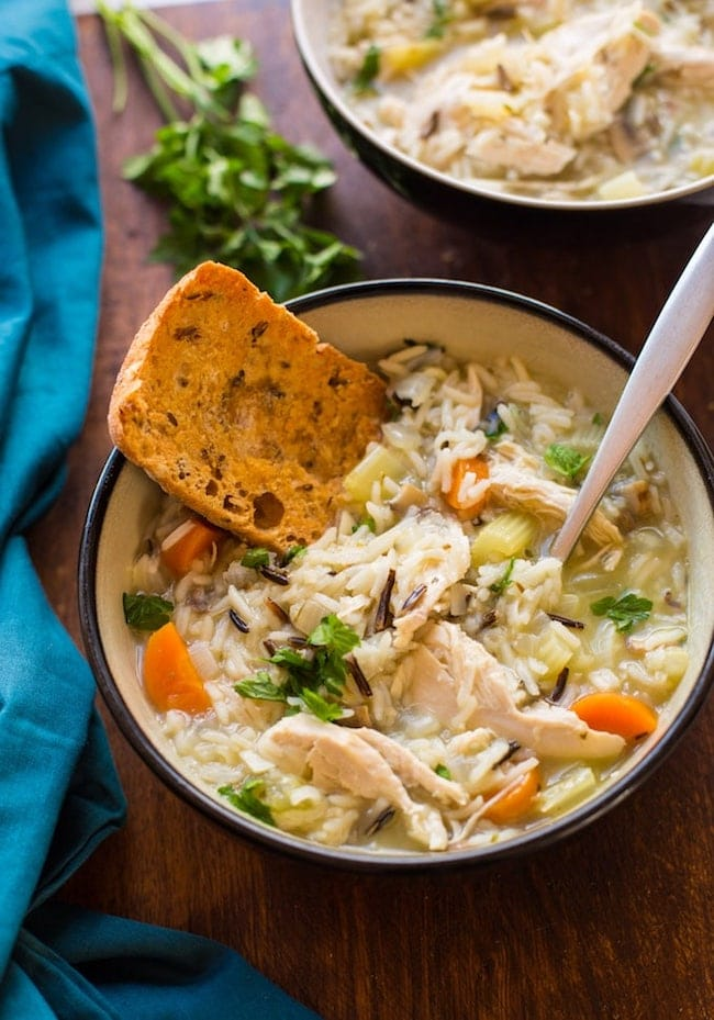 instant pot chicken and wild rice soup with a piece of bread in it