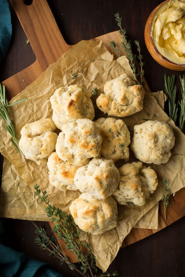 Vegan & gluten free biscuits on a cutting board surrounded by herbs